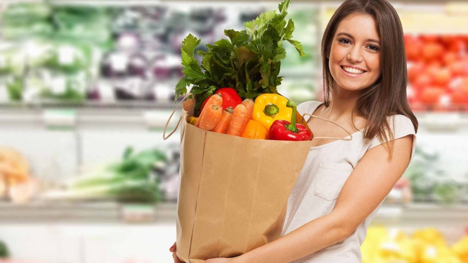 vegetarian woman carrying bag of veggies at the grocery store