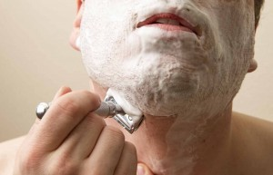 man shaving with a double-edged safety razor