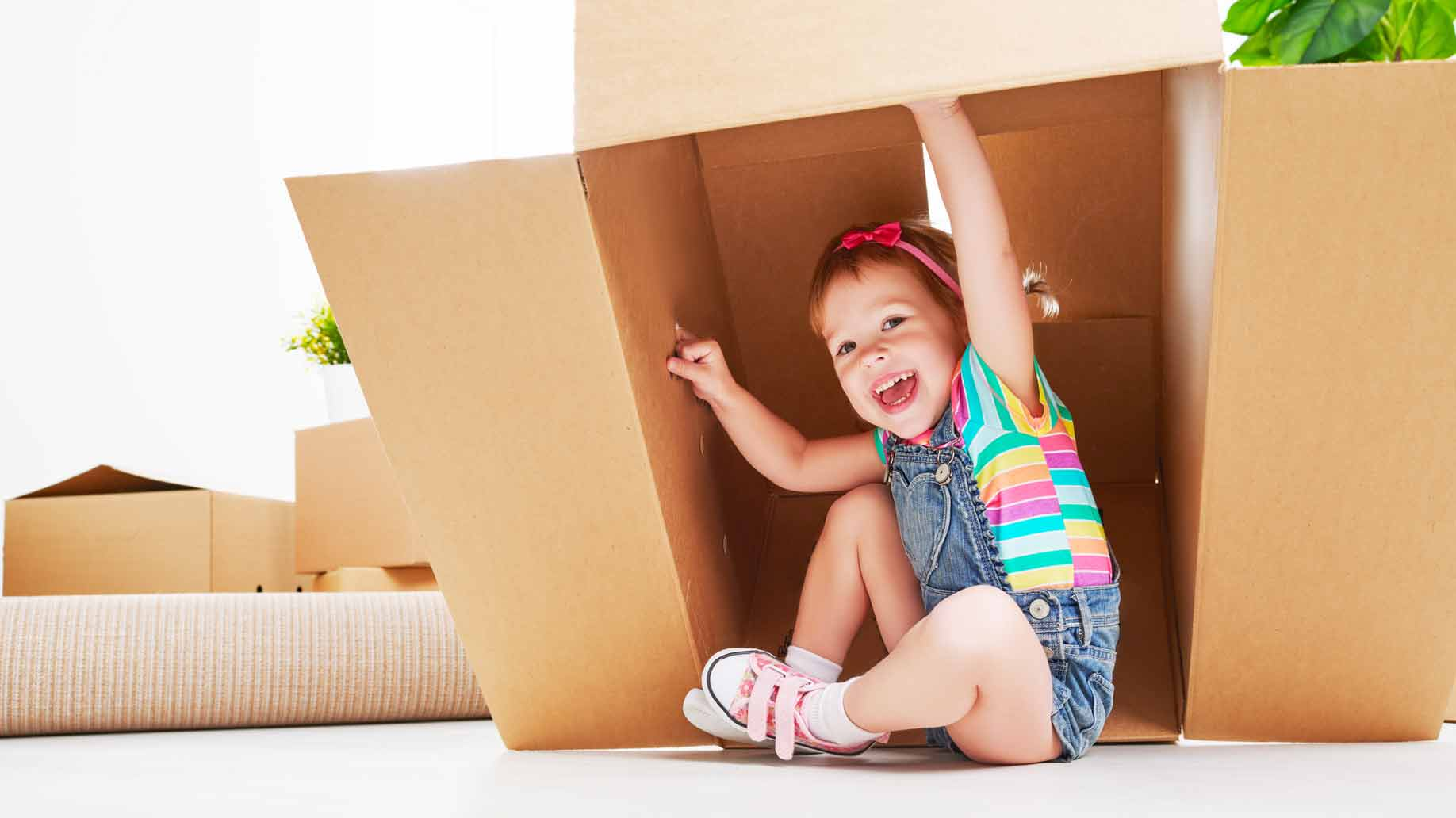 a kid playing in a cardboard box