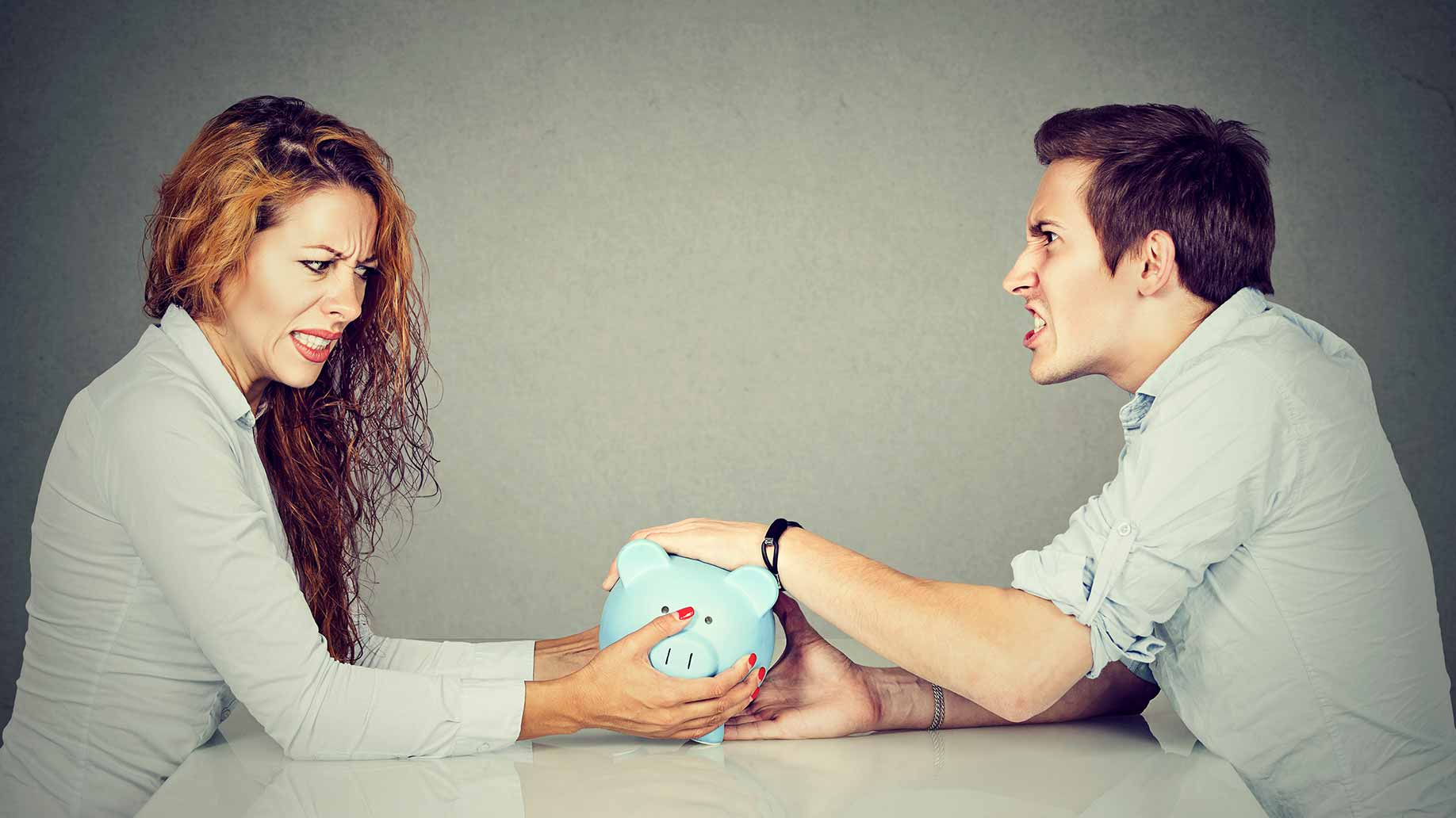 couple fighting piggy bank