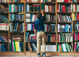 Boy In Library Looking For A Book