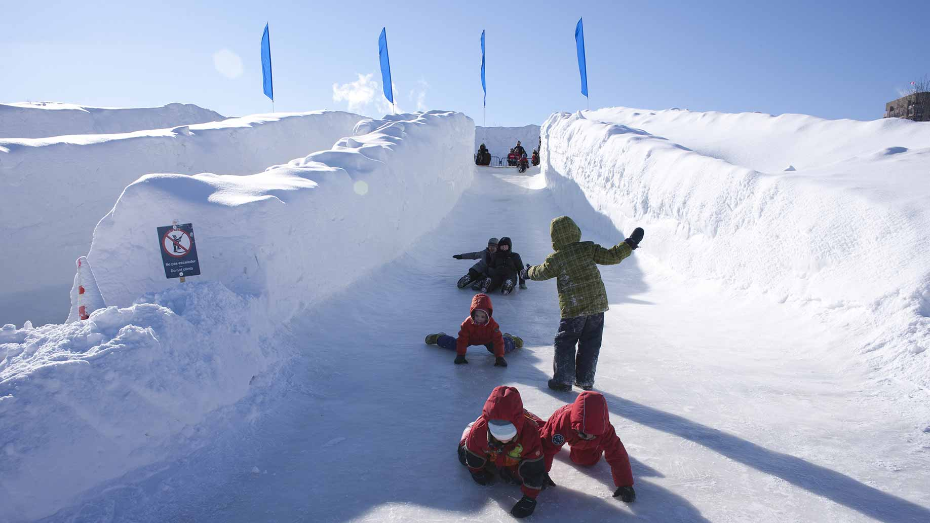 kids sliding down an ice slide at a winter festival in canada