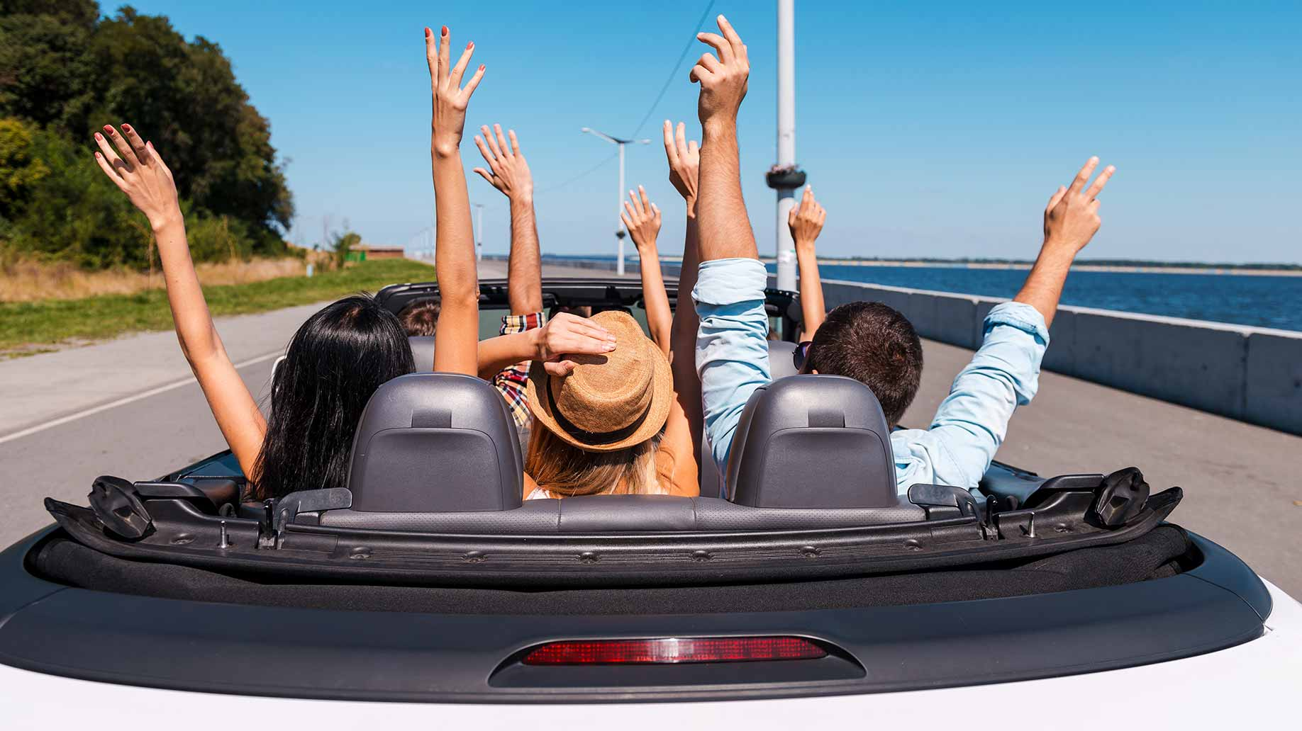 a group of friends driving along the coast in a rental car