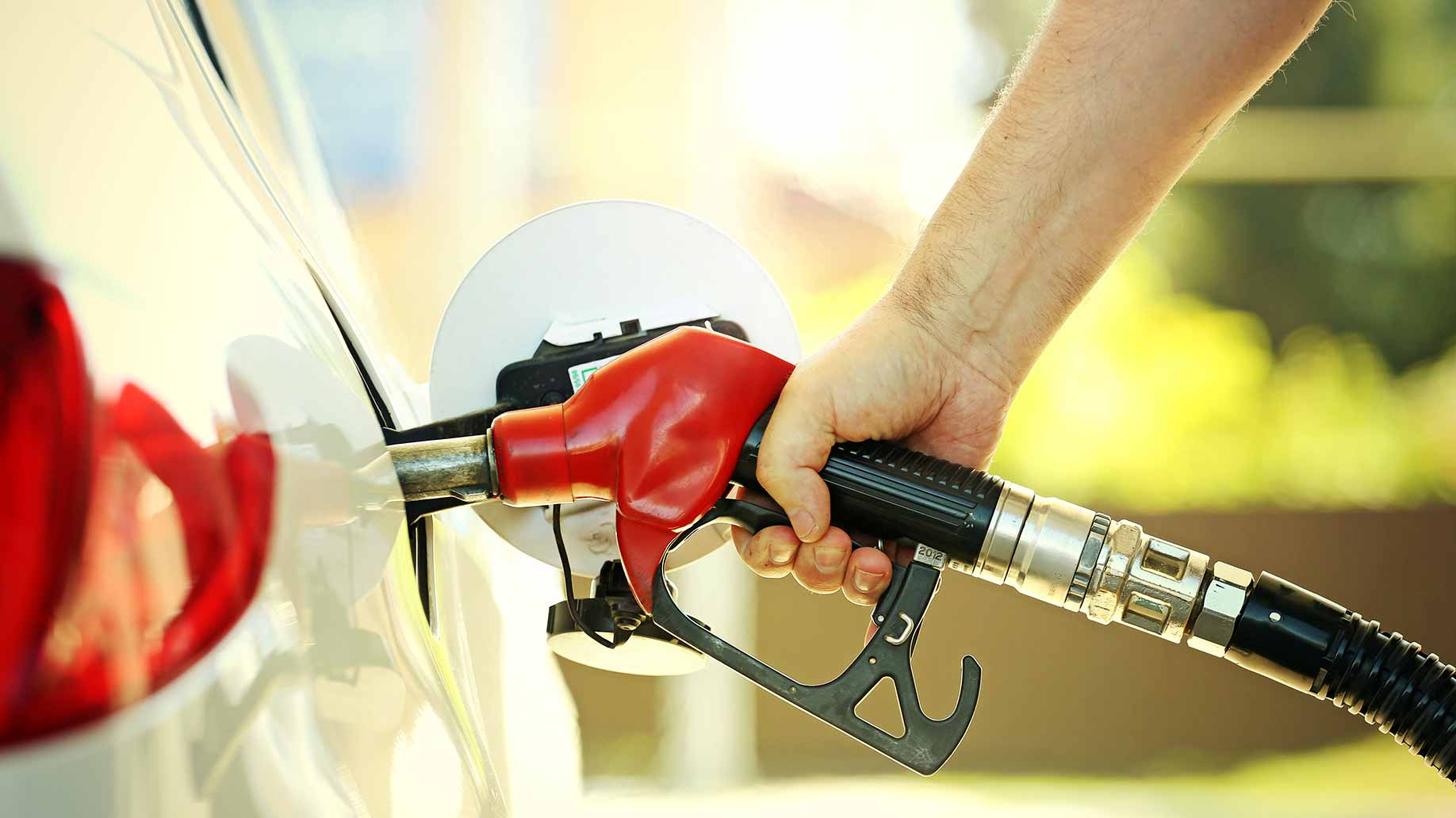a man refuelling his car at a gas station fuel costs
