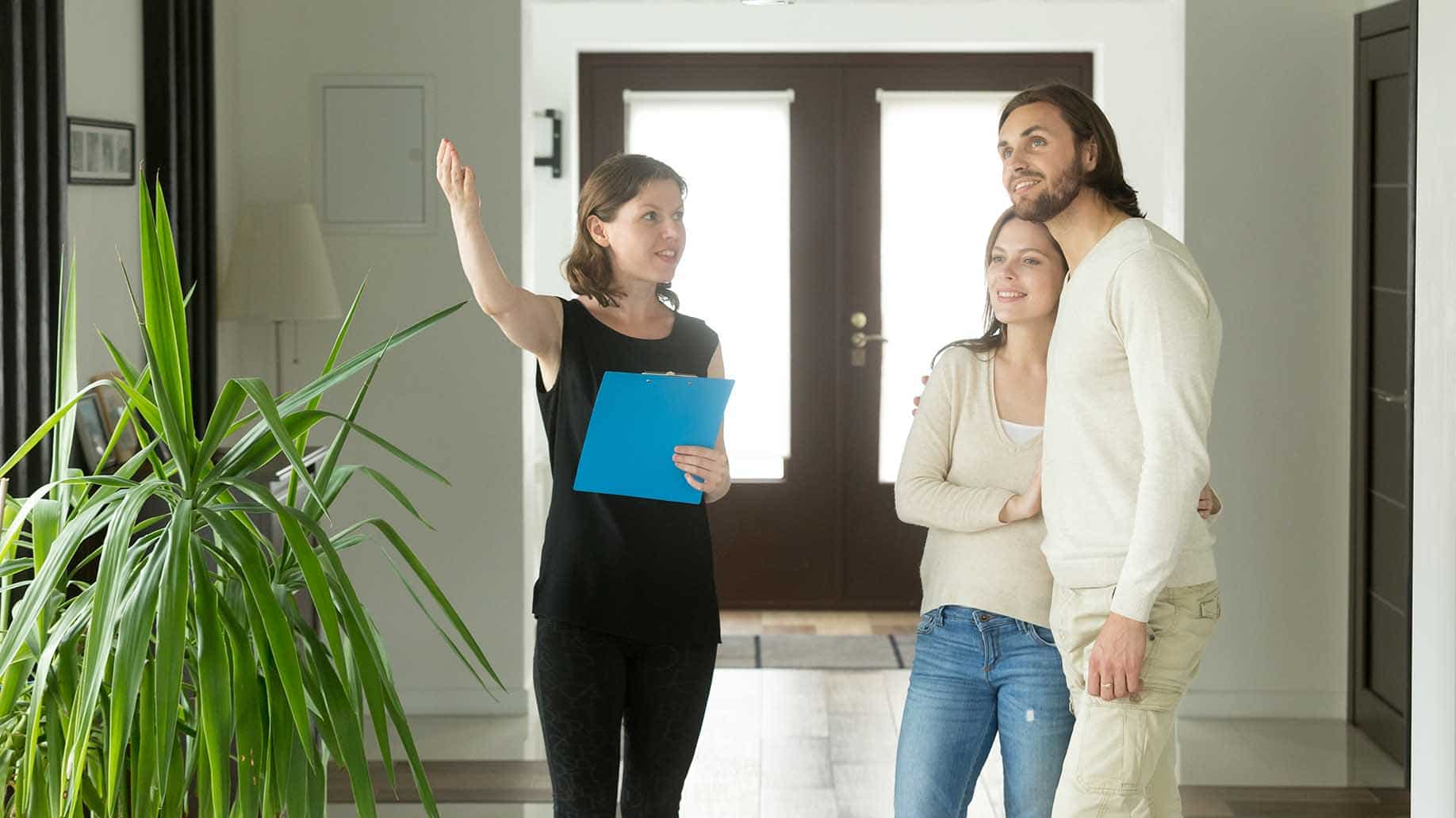couple discussing with real estate agent about house
