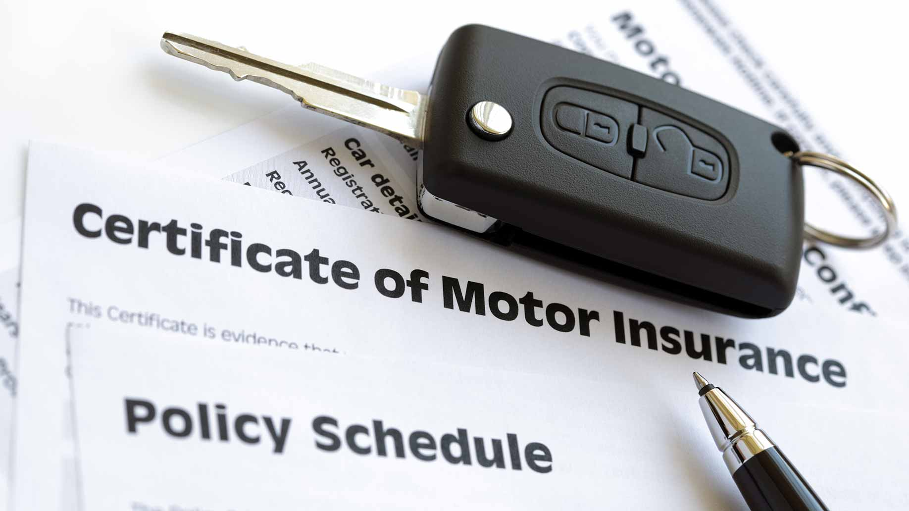 vehicle insurance policy schedule forms on desk with keys