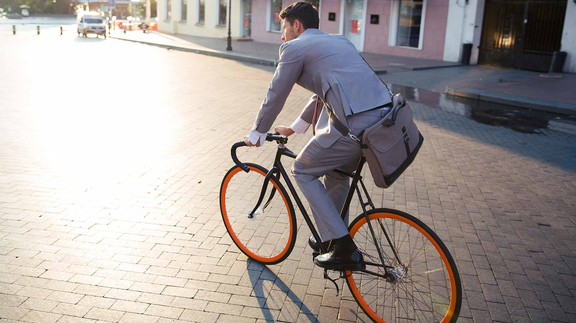 a young businessman in a suit riding a bicycle to work
