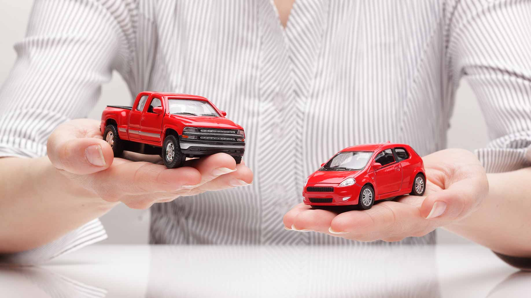 young man holding toy car and truck choosing between vehicles