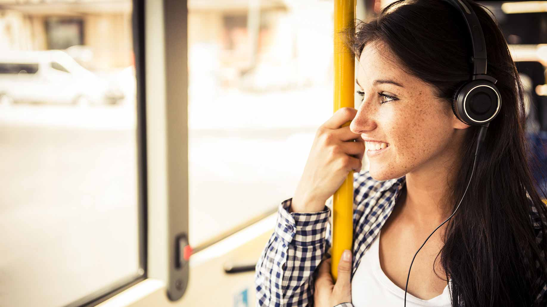 a young woman listening to music on the bus