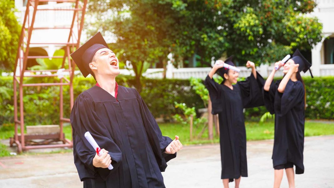 ecstatic male college graduate wearing robe and cap and holding diploma
