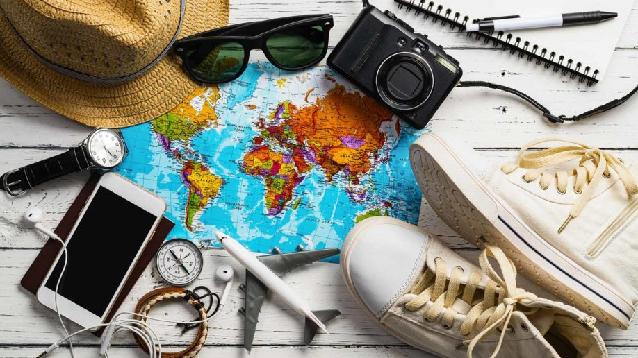 overhead view of travel accessories map camera phone shoes sunglasses hat