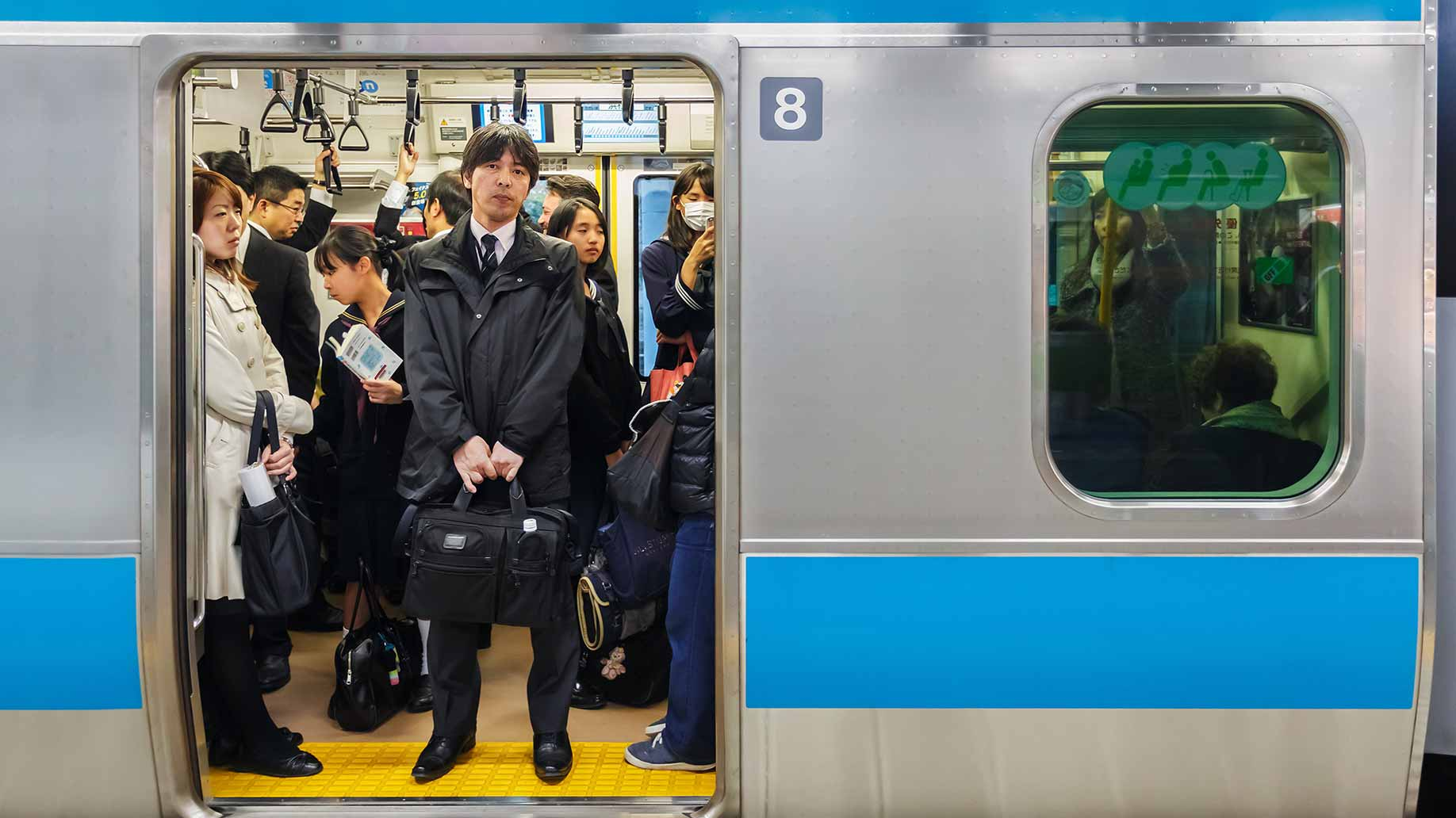 passengers on a commuter train in tokyo, japan public transportation