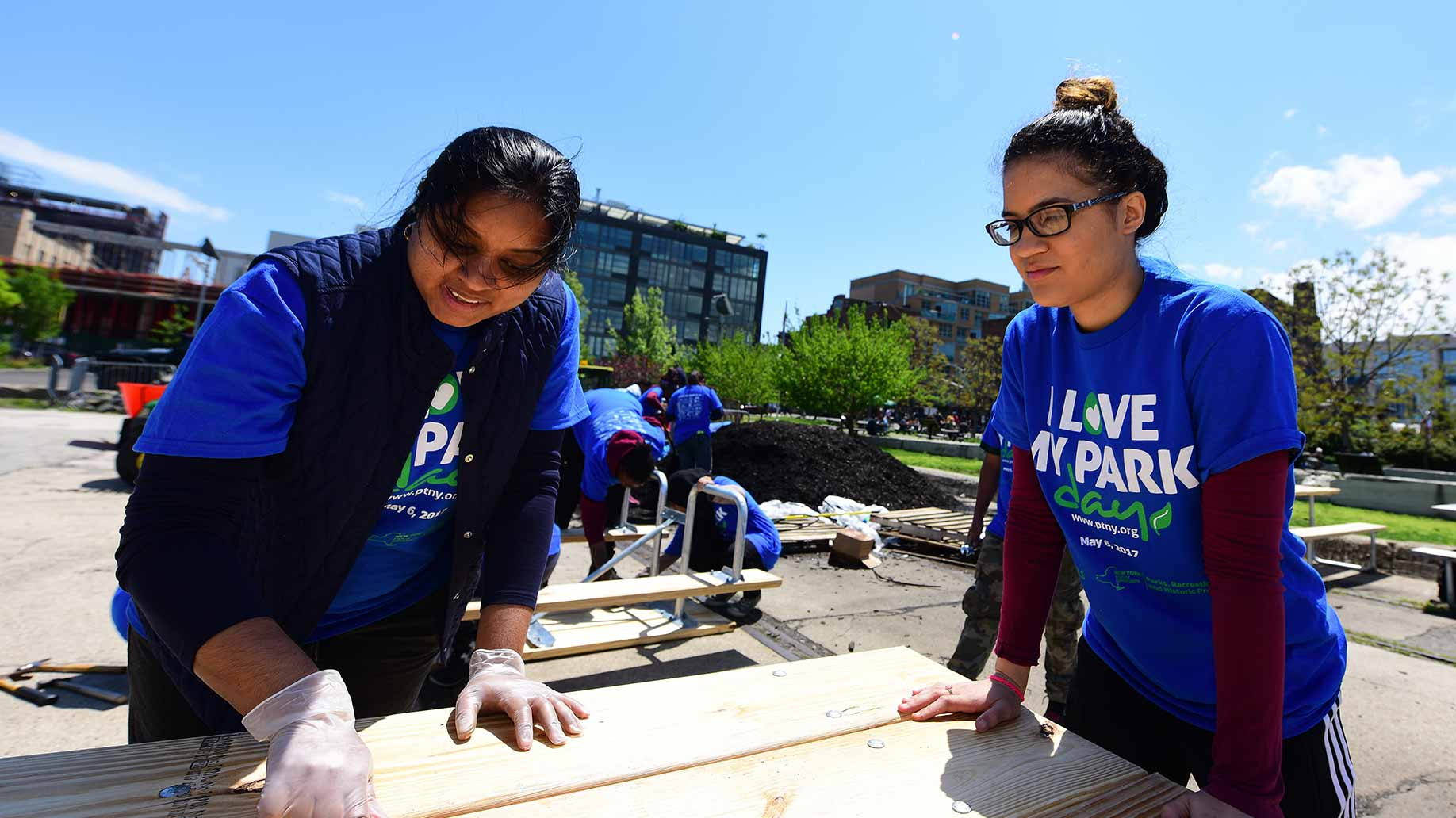 two female americorps volunteers constructing a public bench
