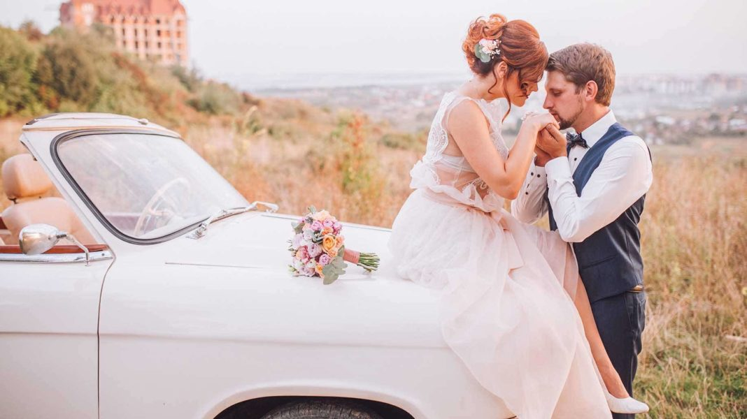 bride and groom sitting on the hood of the car
