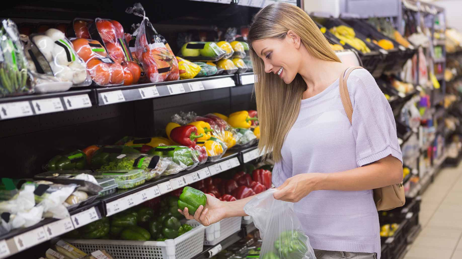 woman buying fruits and vegetables at the grocery store