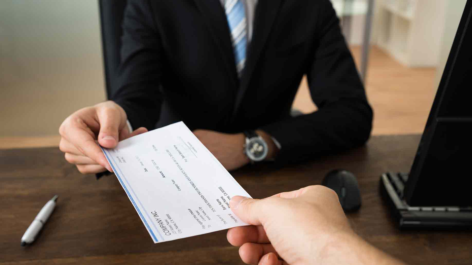 Businessman handing cheque to other person in the office