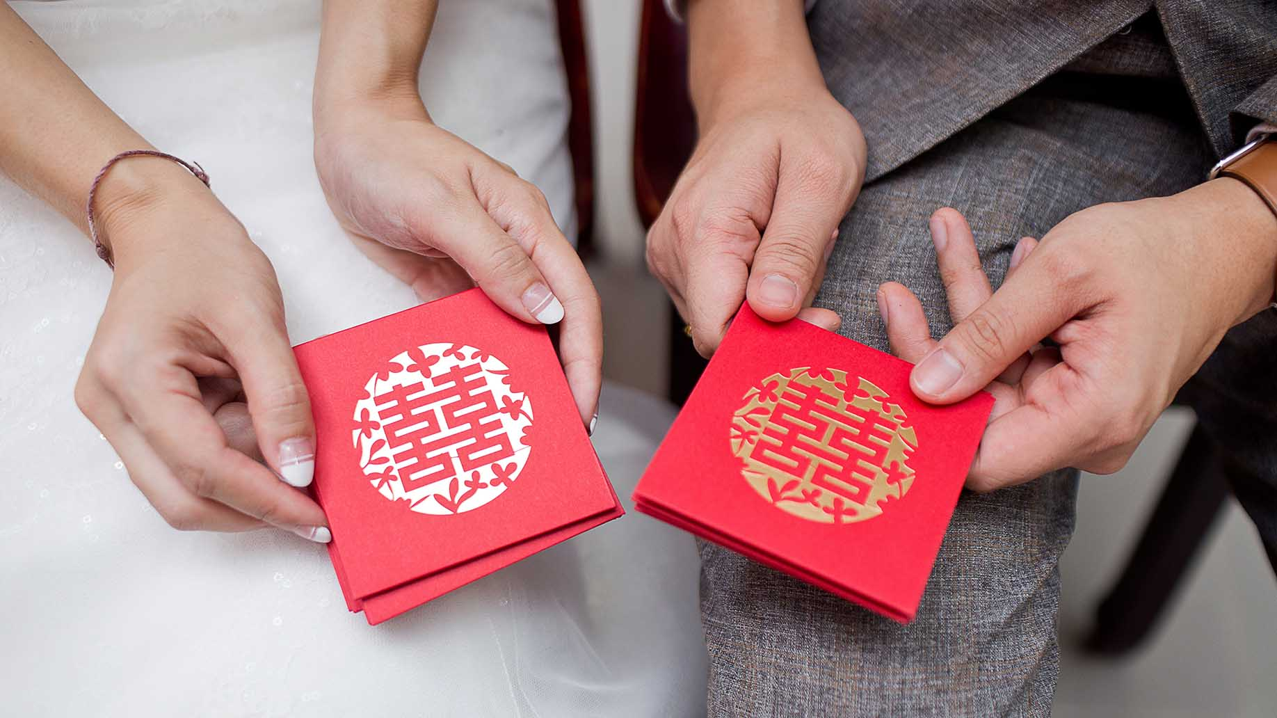 wedding couple holding red envelope packet