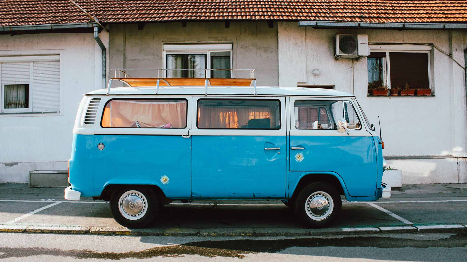 blue and white volkswagen class b motorhome parked on street