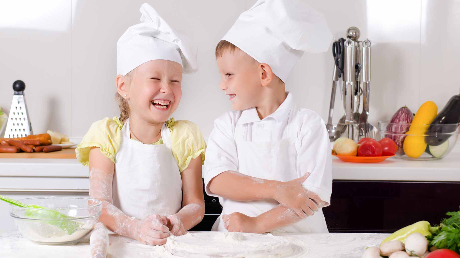 young girl and boy wearing chef hats and making pastry