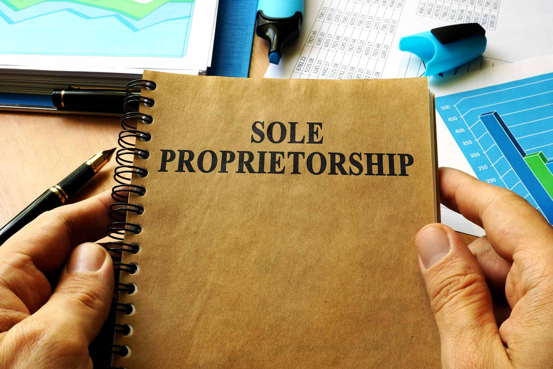 person at desk holding book that says sole proprietorship