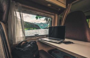 laptop on rv desk with picturesque lake and mountain view