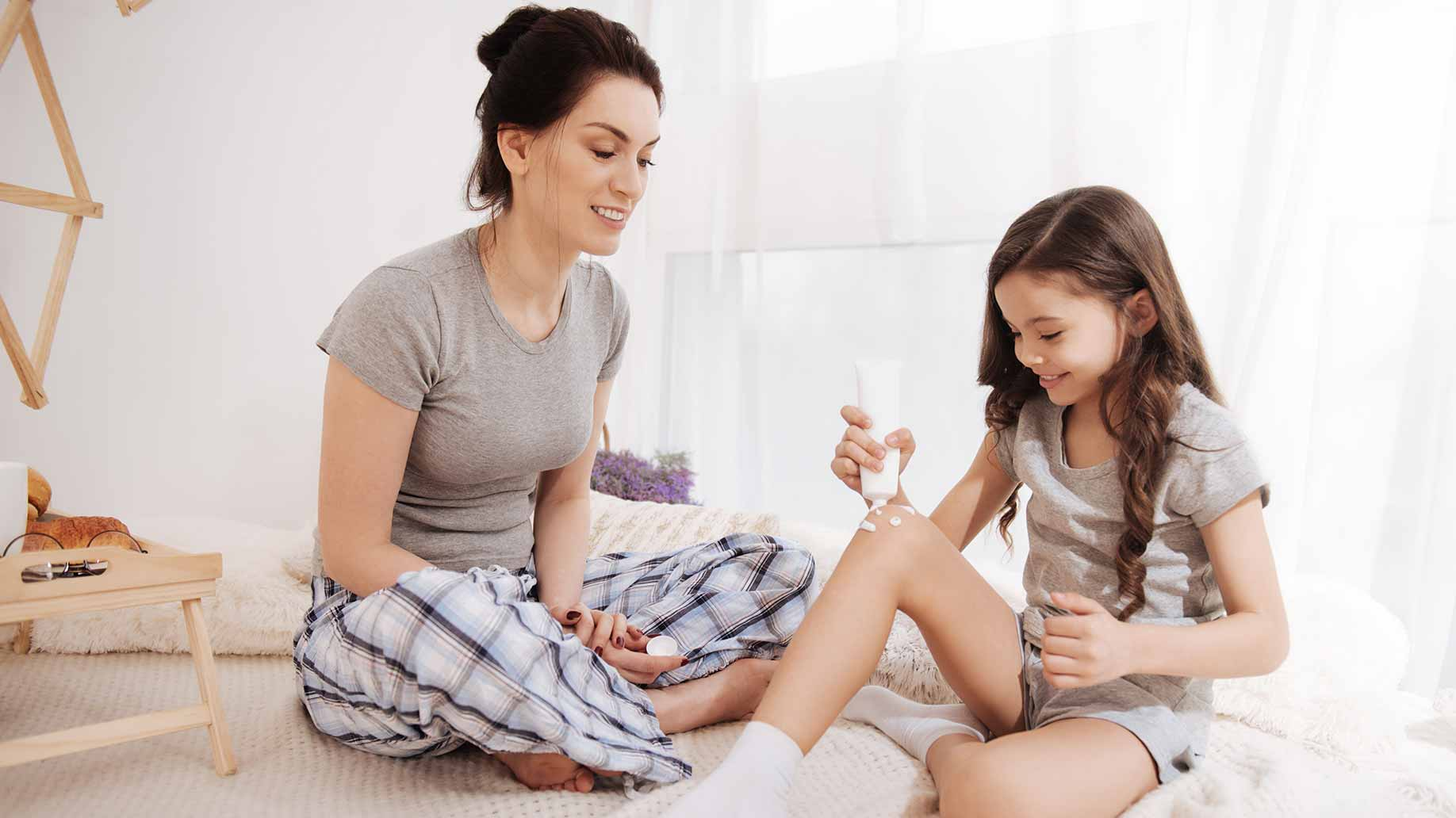 mother daughter testing new beauty product at home