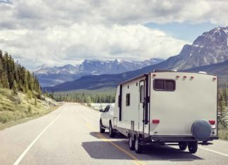 white truck pulling rv along road with mountain view