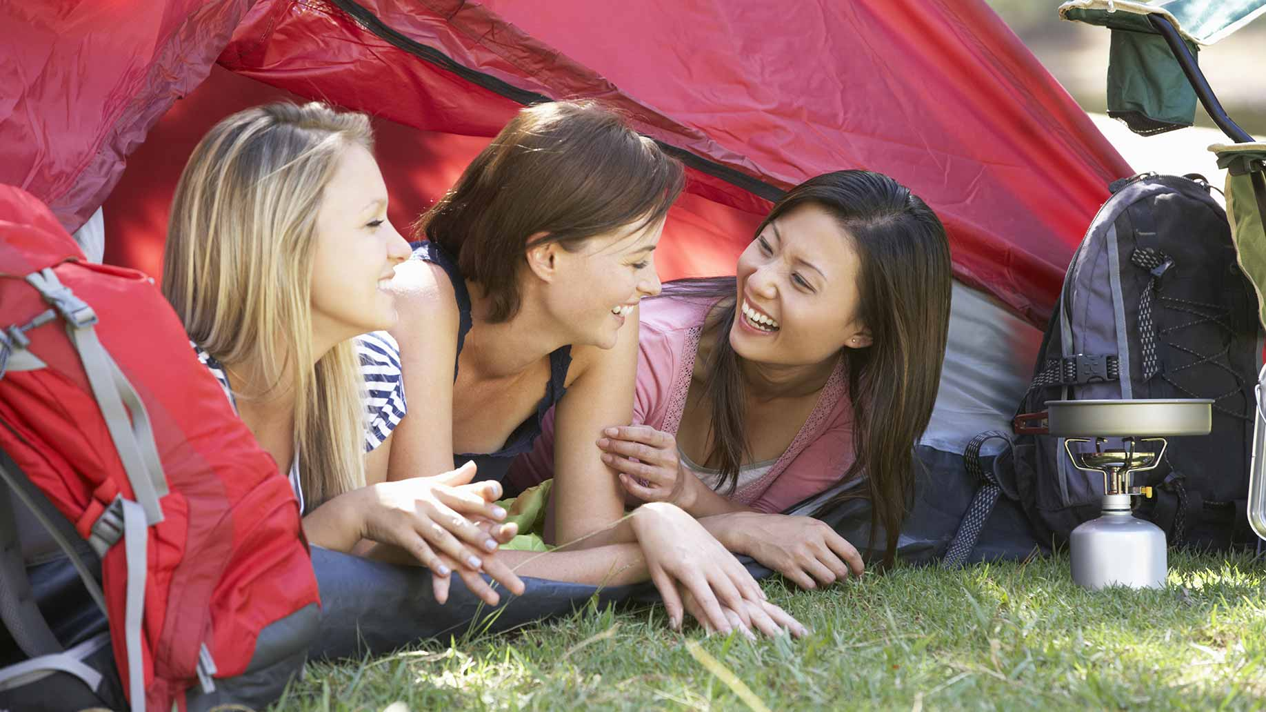 women laughing underneath red tent camping bachelorette party