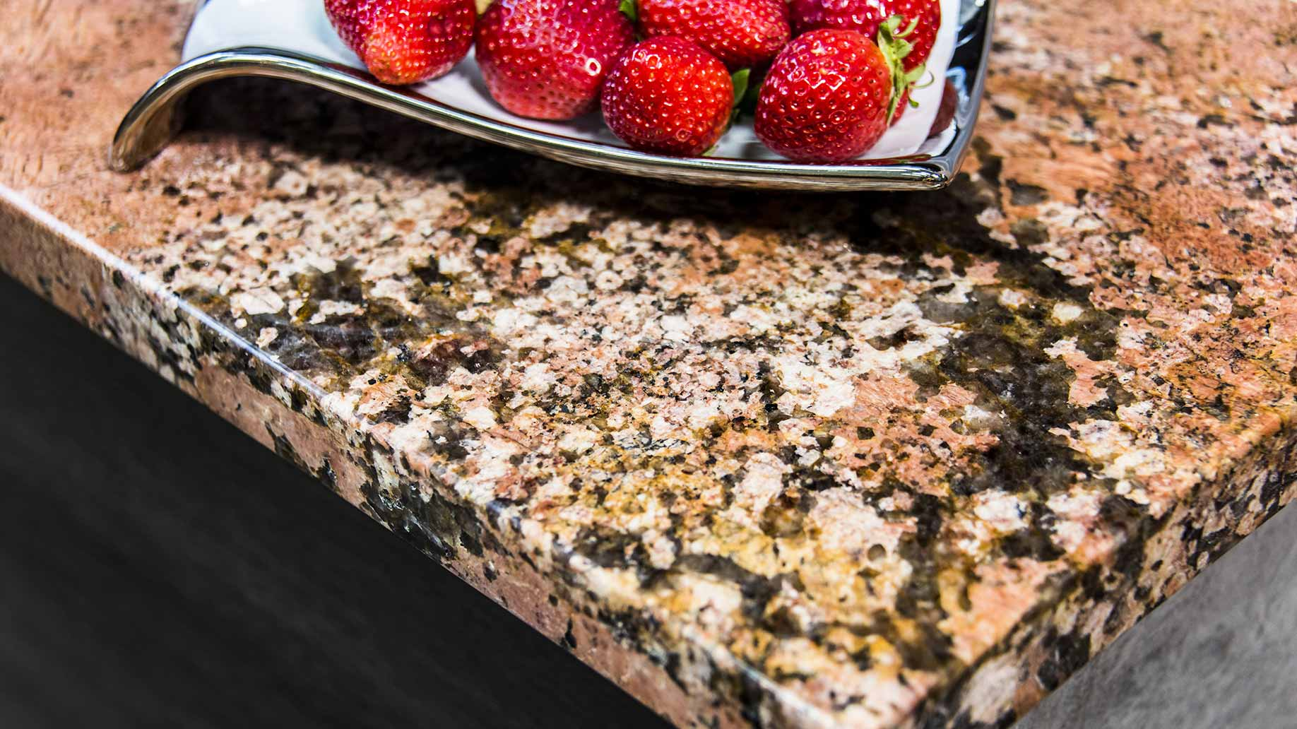 a section of granite countertop with a plate of strawberries