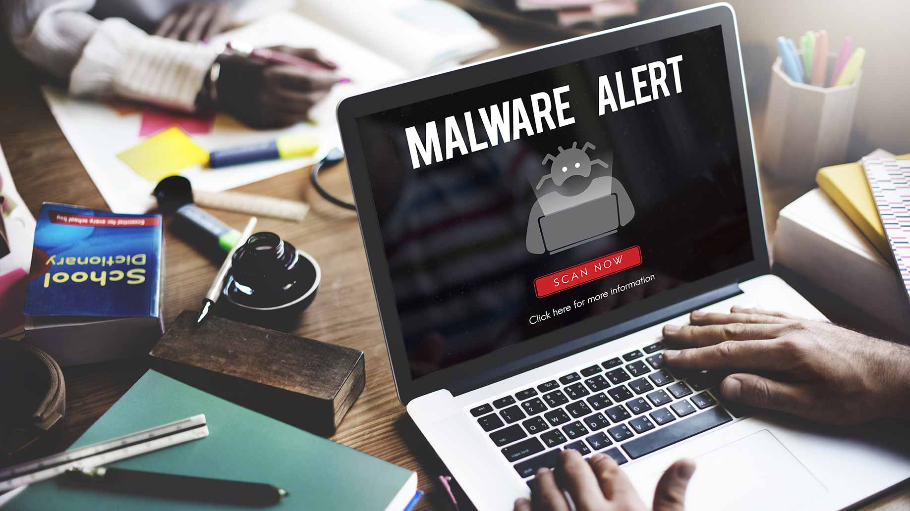 laptop on desk displaying malware virus alert