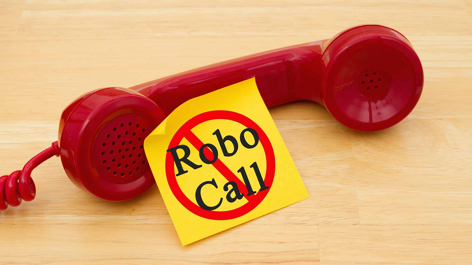 red phone with yellow post-it note displaying no robocall image