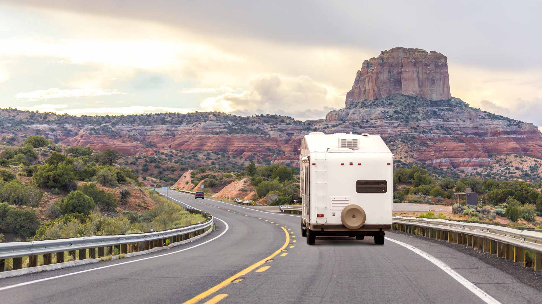 an rv camper traveling down a highway with rock formations in the distance