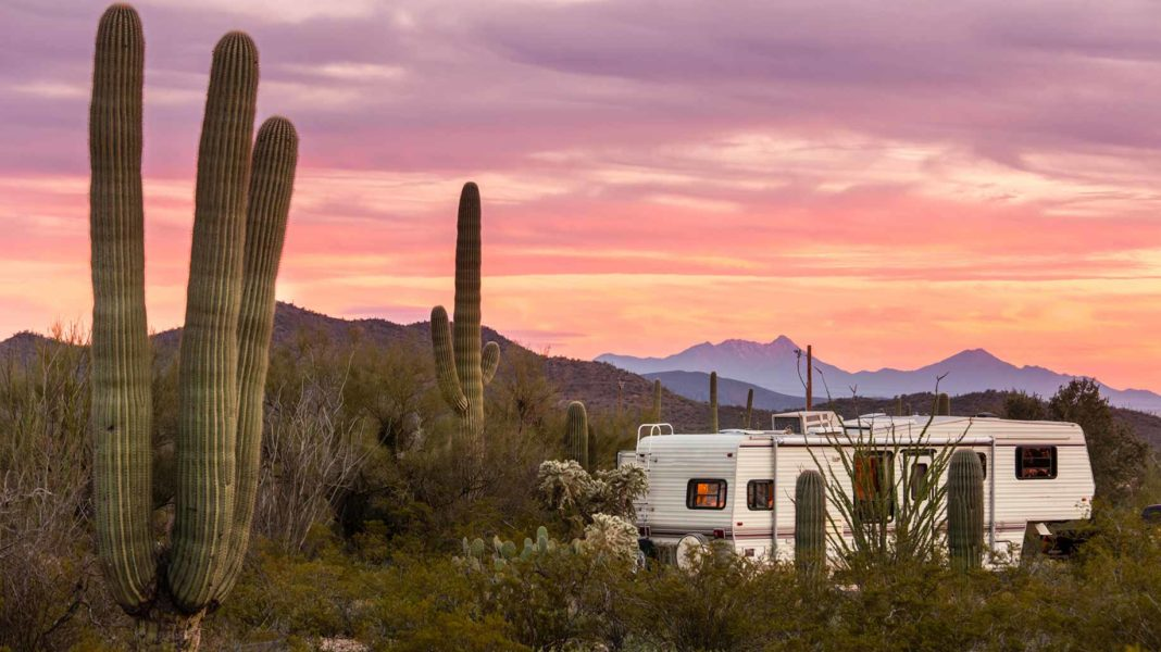 rv camper parked in the sonoran desert at sunset