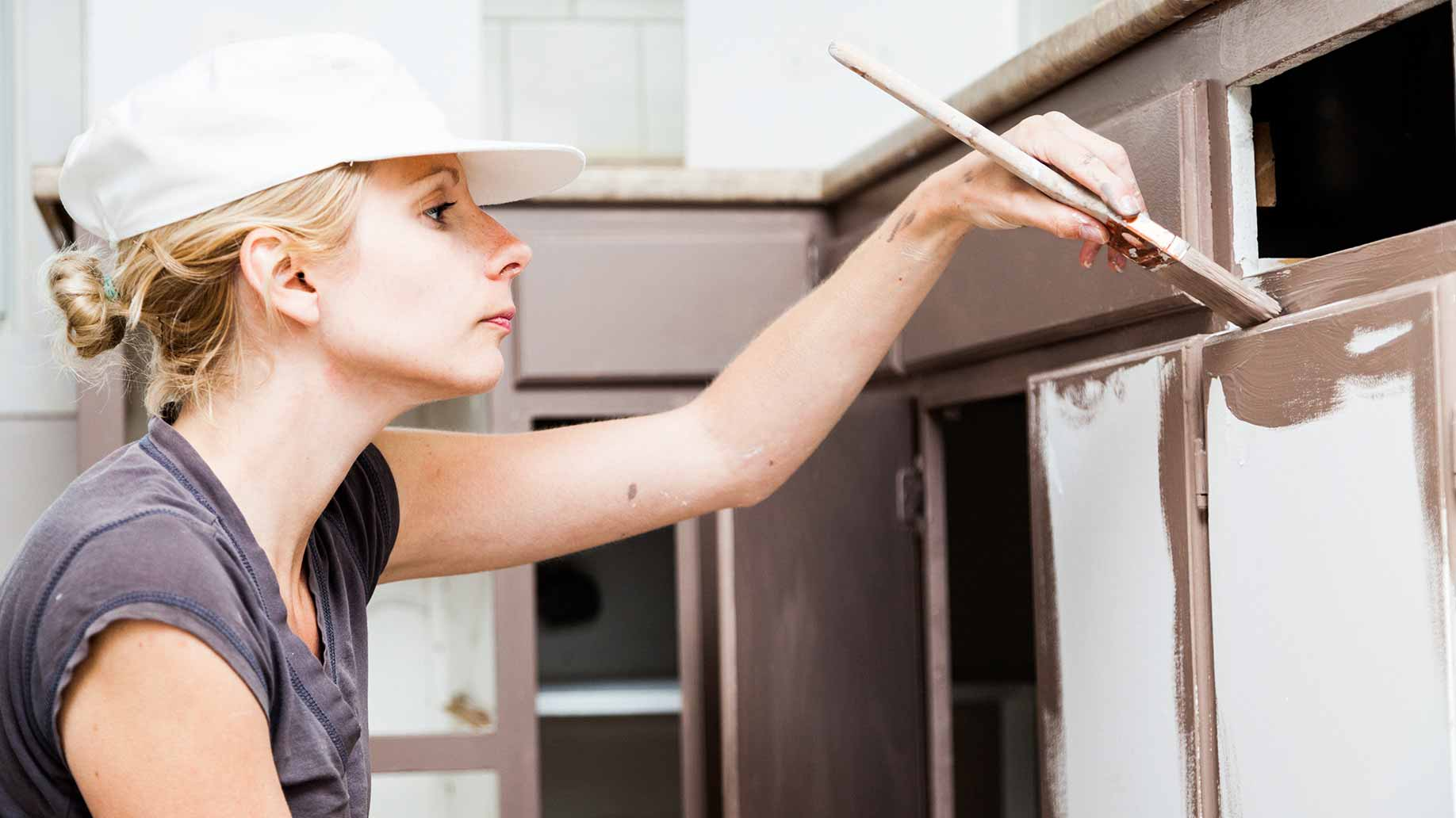 a woman painting her kitchen cabinets diy home renovation