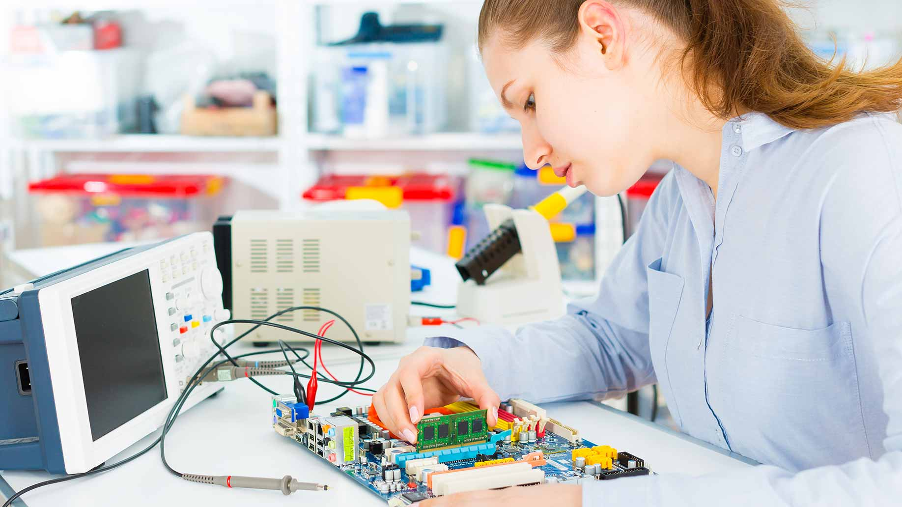 young woman repairing a circuit board in a repair cafe