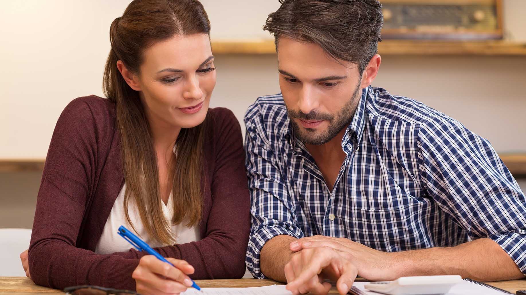 couple analyzing bills discussing their expenses and incomes