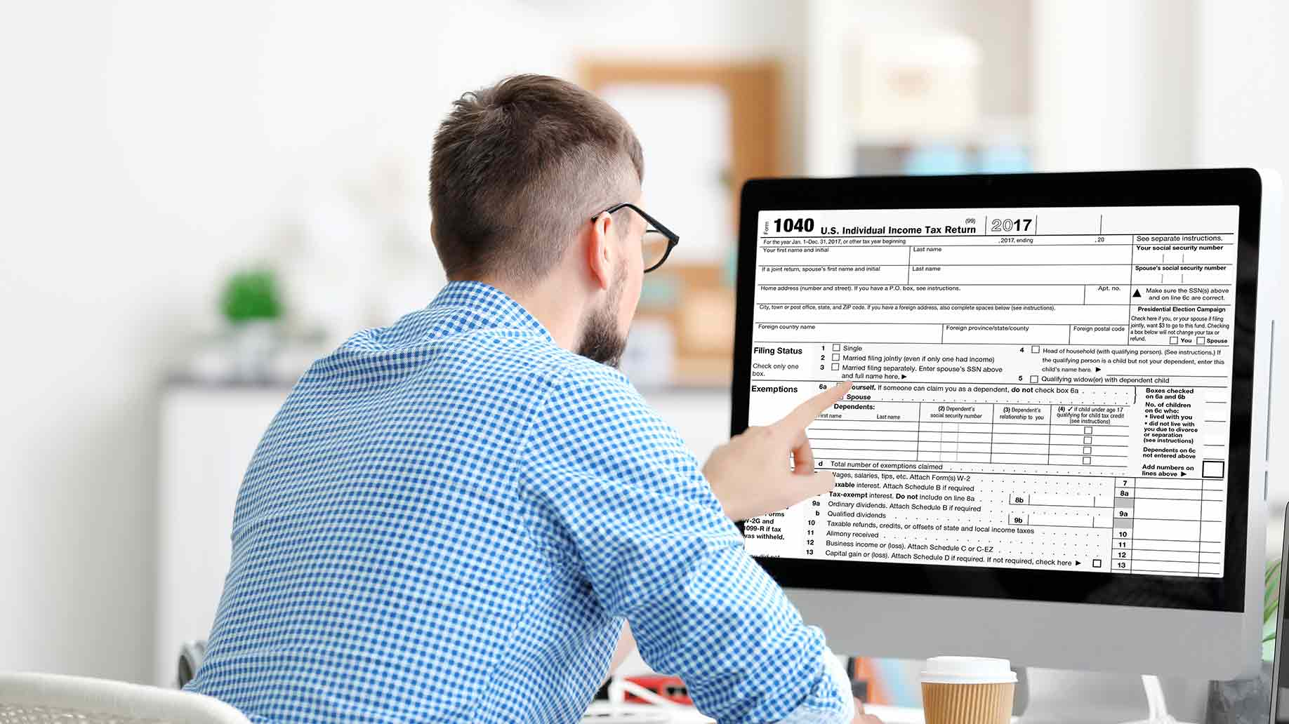 man filing individual income tax return form at table