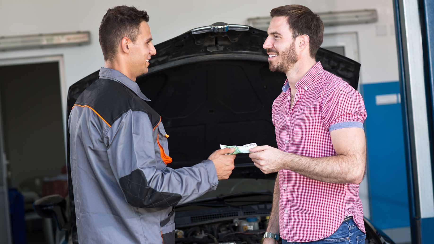 happy man talking to mechanic paying for repair