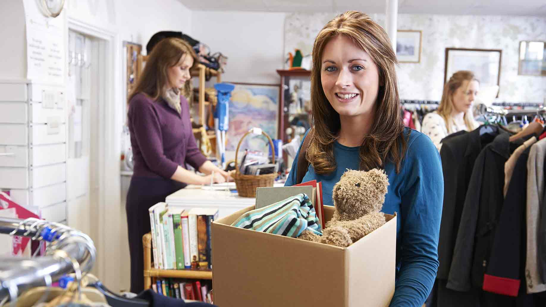 woman donating unwanted items to a charity shop