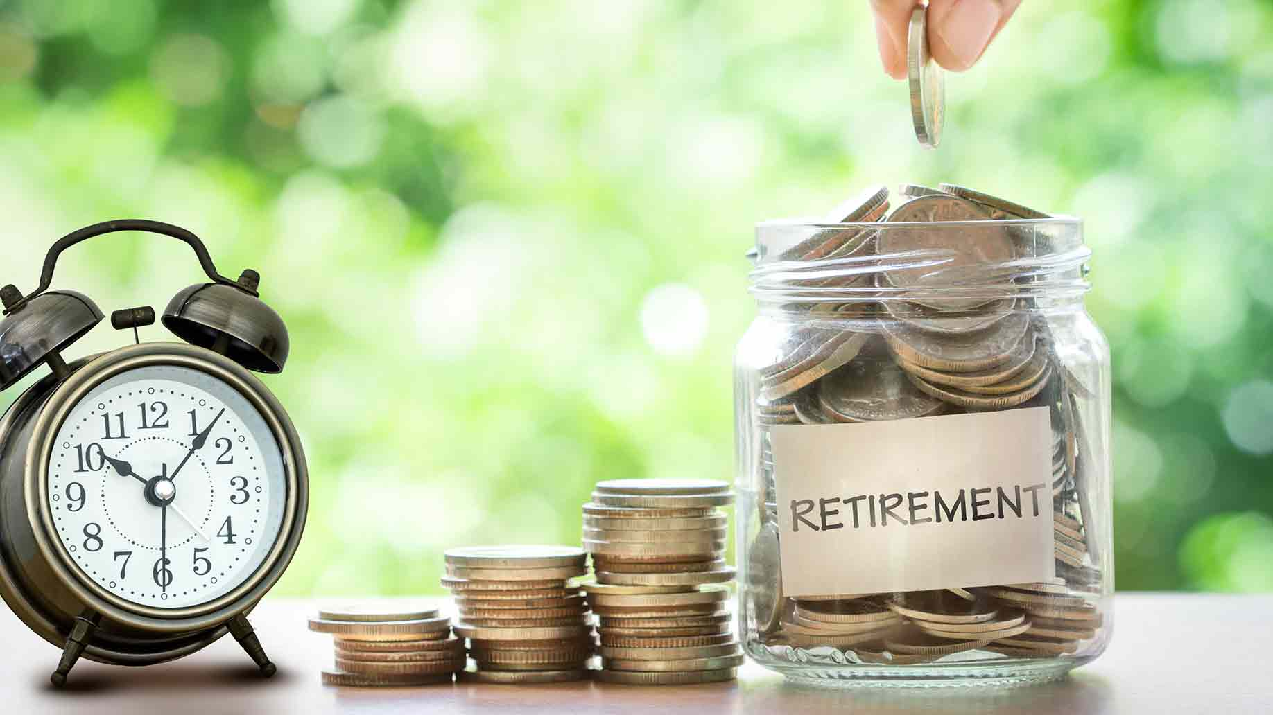 coins in glass jar to save money for retirement with clock