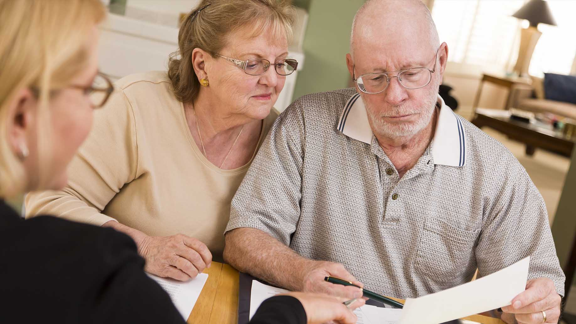 senior adult couple reviewing papers in their home with agent