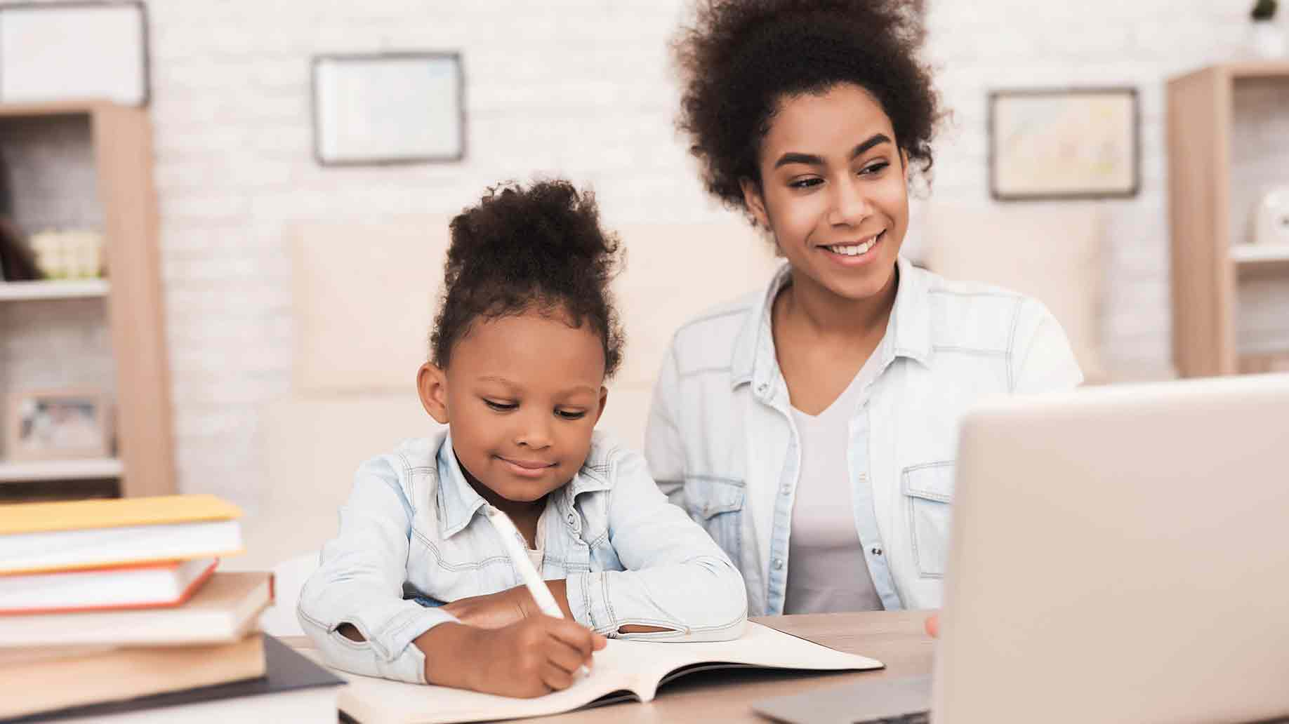 woman and little girl doing homework on the table with computer