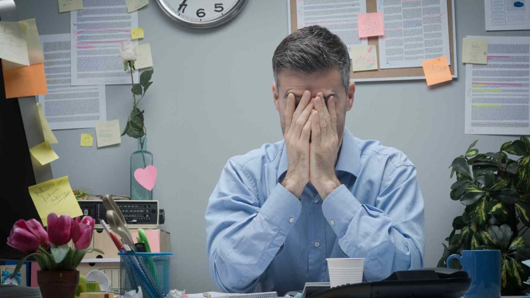 businessman stressed out with face on his palm sitting at his desk