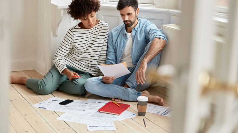 Couple Discussing Paperwork Bills Finances Mortgage House