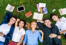 College Students Studying On Lawn Classmates University