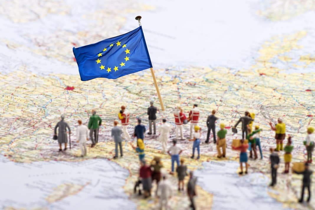 European Union People Figurines Walking On Map Of The Eu Countries