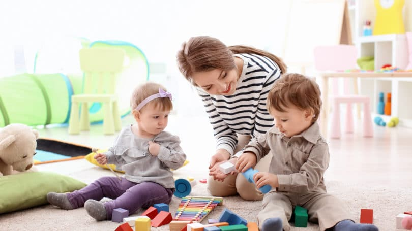 Nanny Babysitter Playing With Children Babies Blocks Playroom