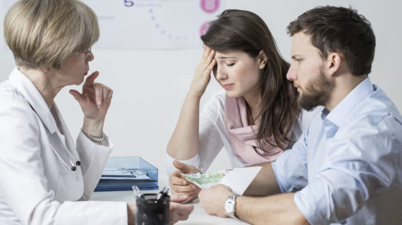 Couple Paying For Ivf Infertility Treatment Doctor Office