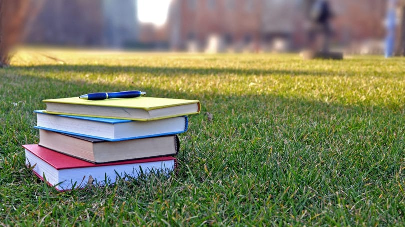 Pile Of Books On College Campus Lawn Grass